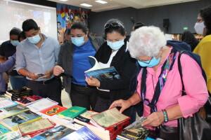 Asistentes del Encuentro en los estands que contienen publicaciones académicas y científicas.