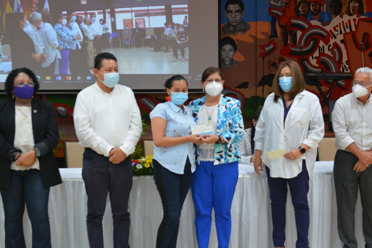 Presidenta de CNU y rectora de UNAN-Managua entrega beca a joven que estudiará en esta alma mater.